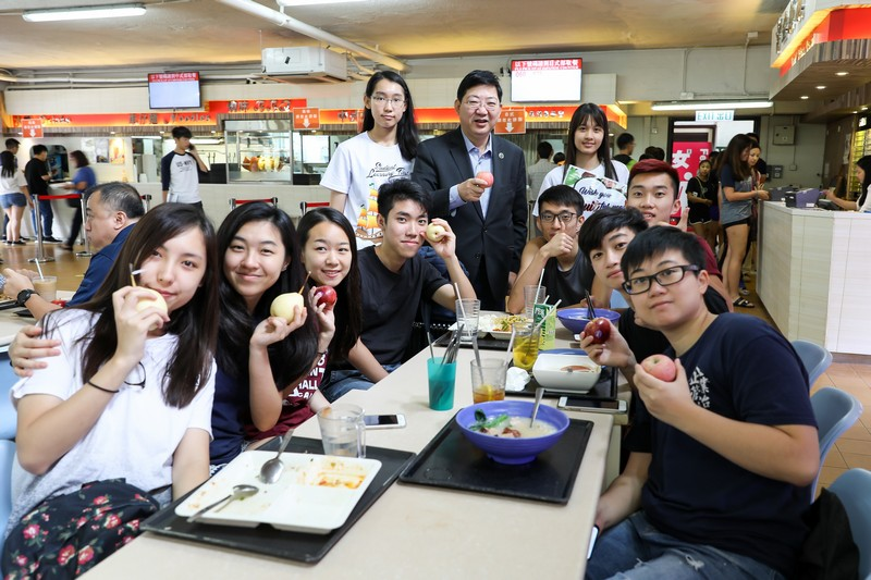 President Simon Ho (middle at the back row) shared fruits with the students at a restaurant and talked with them.