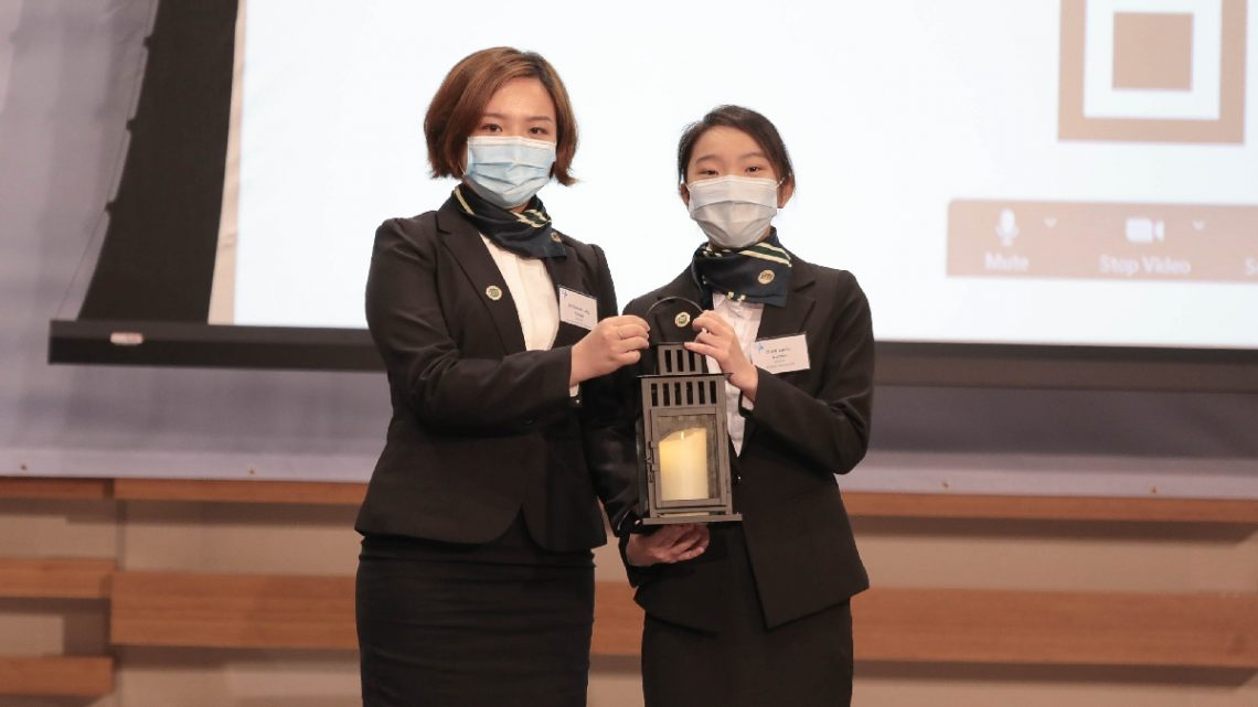 A simple yet solemn handover ceremony – Ms Anthea Chan (right), representative of the new Student Ambassadors, receives the lantern symbolising 'passing on' from her predecessor Ms Vivian Choi (left).