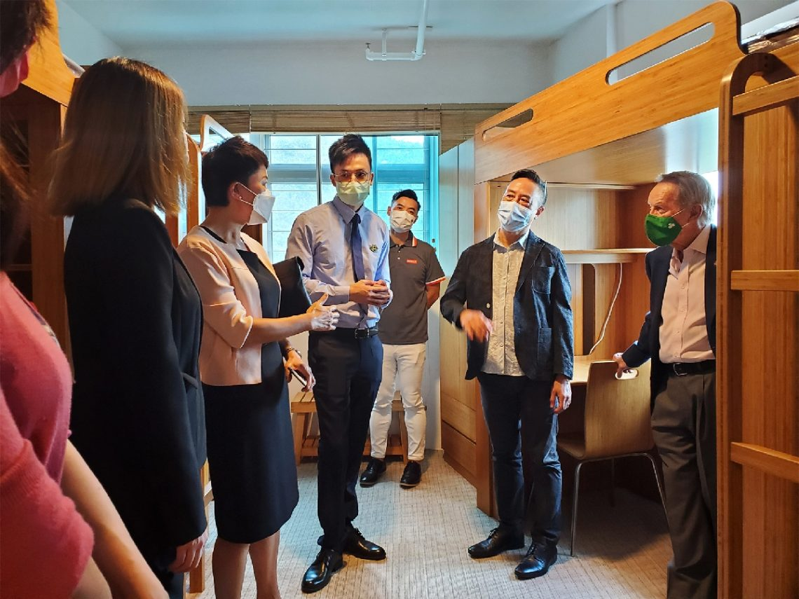 Mr Brandon Wu and Ms Esther Lee showcase a demo 3-student room at the Residential College to the Crown delegation.